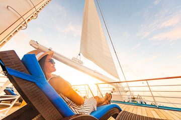 Wall Mural - Luxury cruise vacation woman relaxing in lounger chair enjoying sunset on yacht deck with sail in wind sailing in getaway destination summer travel lifestyle.