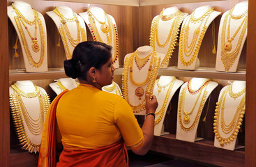 A saleswoman picks gold necklaces to show it to a customer inside a jewellery showroom on the occasion of Akshaya Tritiya, a major gold buying festival, in Kochi