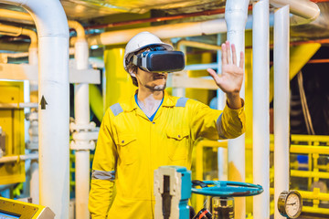 Young woman in a yellow work uniform, glasses and helmet uses virtual reality glasses in industrial environment, oil Platform or liquefied gas plant
