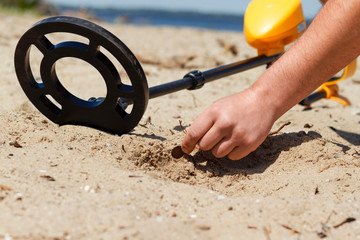 Obraz man with a metal detector on the beach picks up a coin from the sand - fototapety do salonu