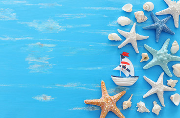 vacation and summer concept with vintage boat starfish and seashells over blue wooden background. Top view flat lay Wall mural