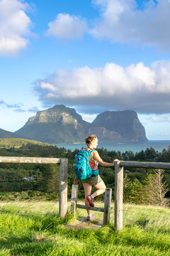 Evening sunset view of subtropical Lord Howe Island in the Tasman Sea, belonging to Australia. Mt Lidgbird and Mt Gower in background.Rear view of beautiful young female hiker with backpack at a fence