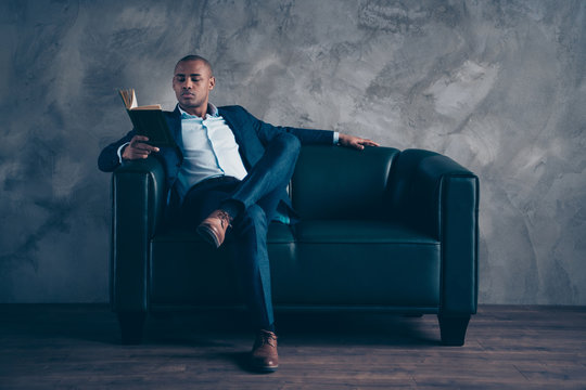 Portrait of his he nice stylish classy elegant chic guy wearing jacket suit director top manager company founder masculine sitting on couch reading psychology at work place station concrete wall