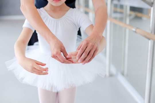 Ballet teacher and little ballerina in classical dancing school. Female dance trainer corrects hands of kid. Practicing for children. Close up.