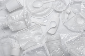 Plastic waste. White single-use plastic products garbage. Top view flat lay.