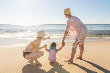 Familie spielt am Strand und schaut aufs Meer
