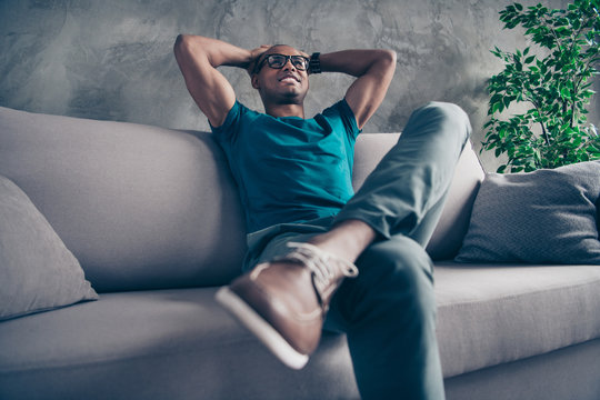 Close up photo amazing he him his dark skin macho handsome hold arms hands behind head pause break excited wear specs casual blue t-shirt pants sit comfy cosy divan modern room office house indoors