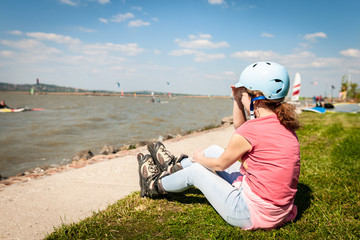 Close up picture of a woman wear inline roller blades near a strand of a lake