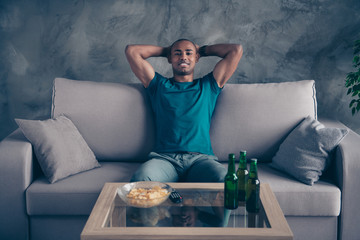 Close up photo amazing he him his dark skin macho handsome hold hands behind head green bottle ale cider potato fried fast food pause break wear blue t-shirt pants sit comfy divan room house indoors