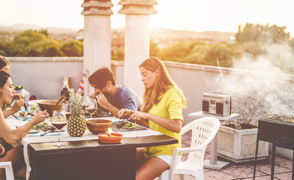 Young friends having barbecue meal at sunset on rooftop patio - Happy people doing bbq dinner outdoor cooking meat and drinking wine - Focus on right woman face - Food, fun and friendship concept