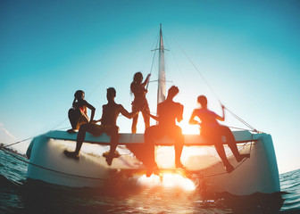Silhouette of young friends chilling in catamaran boat - Group of people making tour ocean trip - Travel, summer, friendship, tropical concept - Focus on two left guys - Water on camera Fotomurales