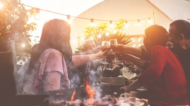 Happy trendy family cheering with red wine at barbecue dinner outdoor - Different age of people having fun at sunday bbq meal - Food, taste and summer concept - Focus on people hands