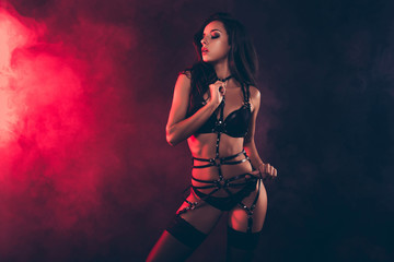 Portrait of lovely magnificent stunning gorgeous charming adorable attractive sporty wavy-haired lady wearing tightening swordbelt teasing isolated over black red light background Fototapete