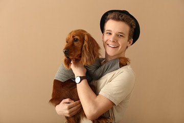Teenage boy with cute dog on color background