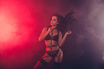 Nice dreamy attractive magnificent fascinating charming sportive perfect figure wavy-haired lady wearing swordbelt teasing posing closed eyes enjoying life isolated on red light black background