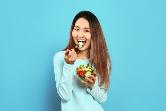 Asian woman with vegetable salad on color background