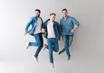 Jumping young men on light background