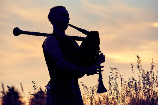 A young modern man plays musical bagpipes outside. Siluet