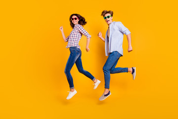 Close up full length body size side profile photo of pair in summer specs he him his she her lady boy jumping high fooling around wearing casual plaid shirt outfit isolated on yellow background Wall mural