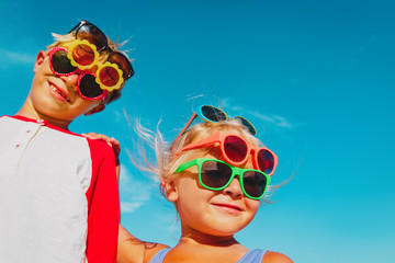 cute little boy and girl try on sunglasses on beach