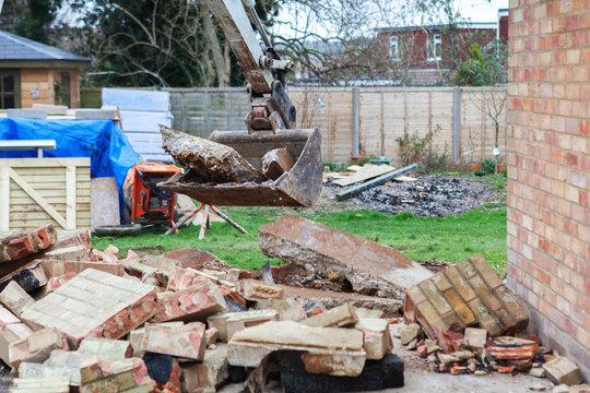 Demolition of the garage in the garden, excavator, selective focus