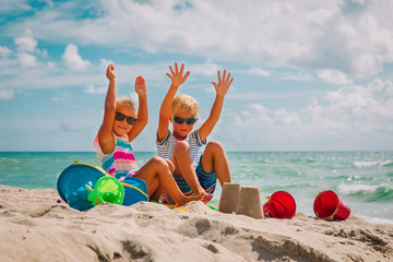 happy kids- boy and girl play with sand on beach