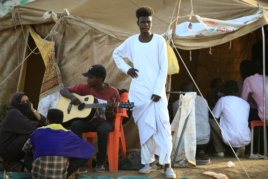 A Sudanese man plays his guitar near the defence ministry compound in Khartoum