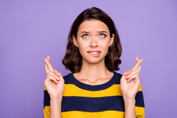 Close up photo beautiful amazing she her lady cross fingers arms hands look up empty space begging win winner victory wear blue yellow striped pullover isolated violet purple background