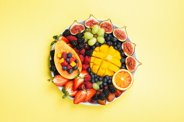 Wall Mural - Delicious fruit platter mango papaya oranges figs berries on round serving plate on yellow background, overhead view, selective focus, copy space