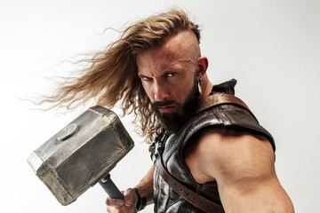 God of thunder. Blonde long hair and muscular male model in leather viking's costume with the big hammer cosplaying Thor isolated on white studio background. Fantasy warrior, antique battle concept.