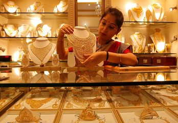 A saleswoman displays a gold necklace inside a jewellery showroom on the occasion of Akshaya Tritiya, a major gold buying festival, in Kolkata