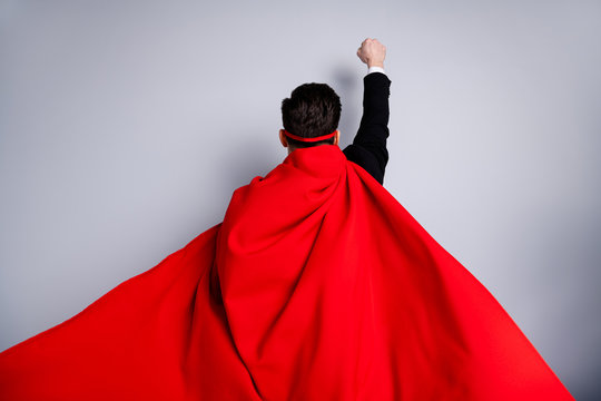 Close up back rear behind view photo hiding facial expression he him his man fist raised up use superpower wear red long cloak raised wind safety protection human race concept isolated grey background