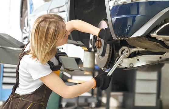 Female mechanic repairing vehicle brake disc.