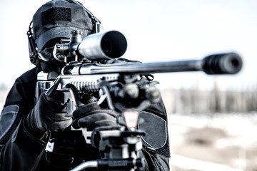 Equipped police SWAT sniper shooting with rifle