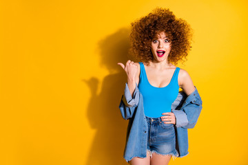 Portrait of her she nice cute lovely winsome fascinating charming attractive cheerful wondered stunned wavy-haired girl pointing aside ad advert isolated over bright vivid shine yellow background Wall mural