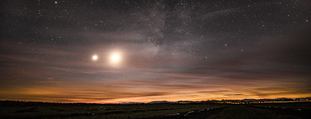 The moon, planet Venus, and the Milky Way galaxy shining through a thin layer of clouds at dusk, over an agricultural field in Northern California