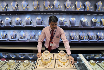 A salesman displays gold necklaces and earrings inside a jewellery showroom on the occasion of Akshaya Tritiya, a major gold buying festival, in Mumbai