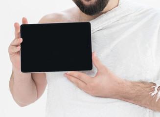 Adult Hajj holding tablet