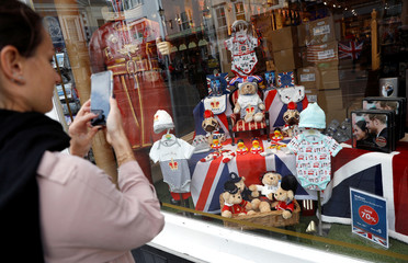 A woman takes a picture of baby clothes and other articles displayed in a shop window, in Windsor