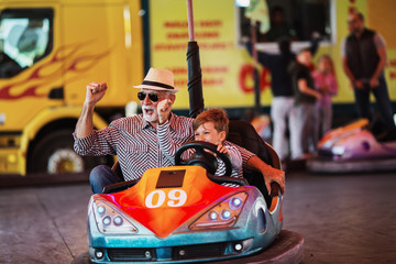 Foto op Aluminium Amusementspark Grandfather and grandson having fun and spending good quality time together in amusement park. They enjoying and smiling while driving bumper car together.