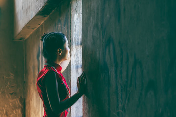 Portrait images of Chinese girl wearing red cheongsam dress Standing in an abandoned building, to Instagram concept.