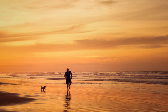 Silhouette of man running with dog in the beach in sunset time