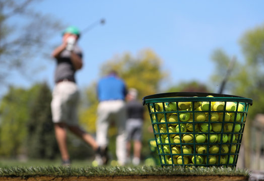 A jumbo bucket of golf balls sit at the end of a golfing practice facility