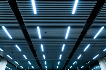 Leading lines and low light view. Fluorescent lamps open in row on the ceiling beautiful and modern inside the building. Wall mural