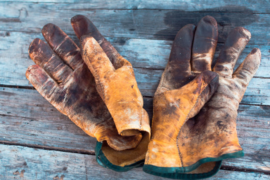 Old dirty work gloves on a wooden table stained with grease and oil. Representation of high risk and hard work professions