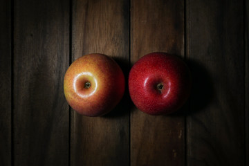 two apples bottom view on wooden table.