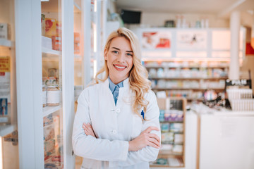 Cheerful pharmacist standing in pharmacy drugstore.
