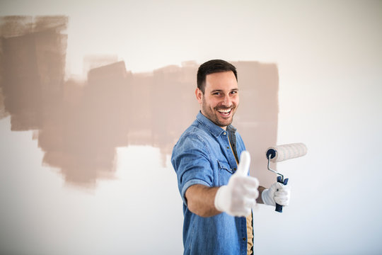 Handsome man painting wall with roller.