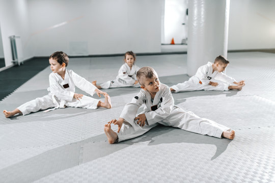 Small group of Caucasian sporty children stretching and warming up before their taekwondo training.