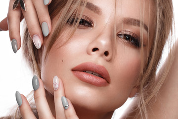 Pretty girl with easy hairstyle, classic makeup, nude lips and manicure design. Beauty face. Art nails.